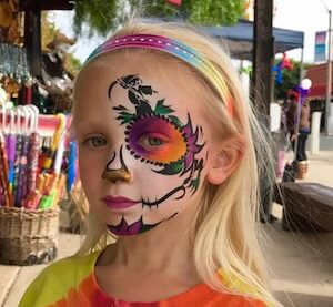 Child with Stencil of Grim Reaper incorporated into her Sugar Skull Face Painting