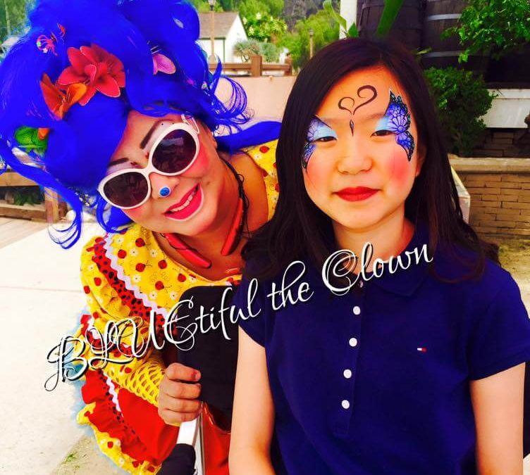 Bluetiful the clown with a girl she face painted as a butterfly at Old Town San Diego Marketplace
